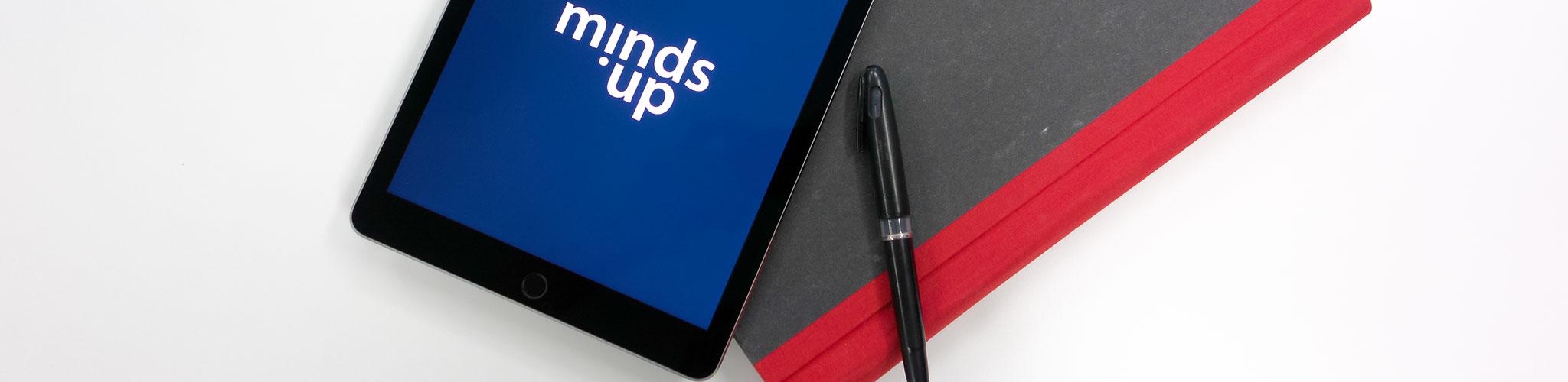 iPad mit Buch und Stift und mindsup.de Logo